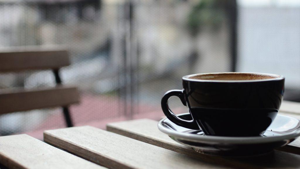 Ein Kaffee steht auf dem Bistrotisch
